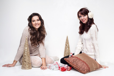 Happy girls sitting in christmas house on white background photo
