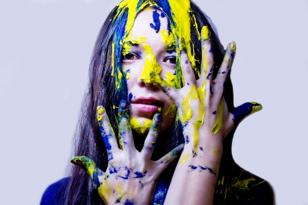 Beauty fashion close up portrait of woman painted blue and yellow on white background photo
