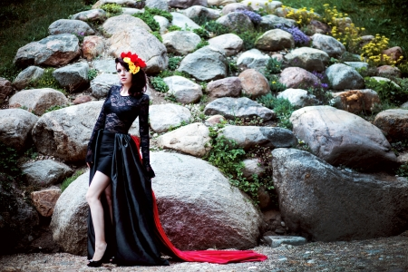 Woman in black and red lace dress and flowers on stone outdoor Stock Photo - 24455141