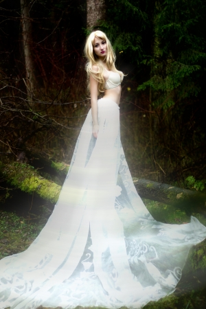 Blonde bride angel in long white skirt standing in dark forest photo
