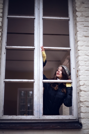 fearing: Beautiful woman looking through the window and fearing of something