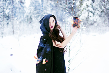 Witch or woman in black cloak with fire ball in white snow forest photo