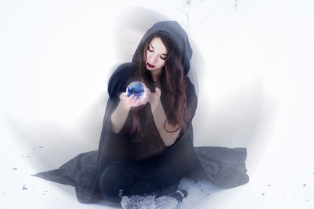 Witch or woman doing magic in black cloak with glass ball in white snow forest photo