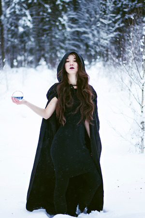 Witch or woman in black cloak with glass ball in white snow forest photo