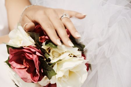 brides hand with wedding ring on bridal bouquet Stock Photo