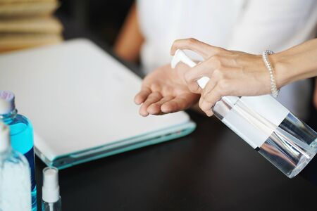 woman spraying alcohol gel or antibacterial soap sanitizer on Friend's hand at office.Hygiene concept. prevent the spread of germs and bacteria and avoid infections coronavirus