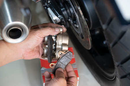 Mechanic using a wrench and socket on motorcycle sprocket   .maintenance,repair motorcycle concept in garage .selective focus