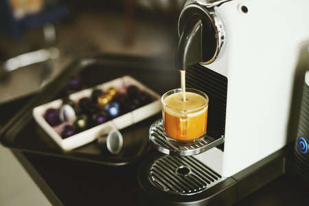 Espresso maker machine breuuing coffee in a glass cup with capsules on white desk at office in the morning