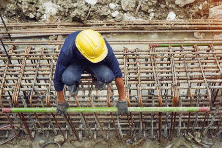 Construction workers wearing safety helmets at Work ,sitting on steel reinforcement bar and holding steel pipe,scaffolding pipe clamp and parts at the construction site.