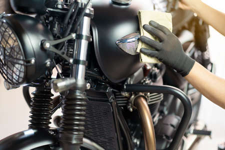 Biker man cleaning motorcycle , Polished and coating wax on fuel tank. repair and maintenance motorcycle concept.