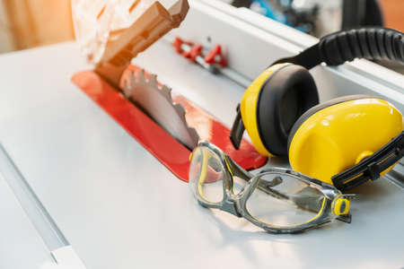 Safety glasses and Earmuffs on Electric saw table in workshop .Work safety concept . selective focus