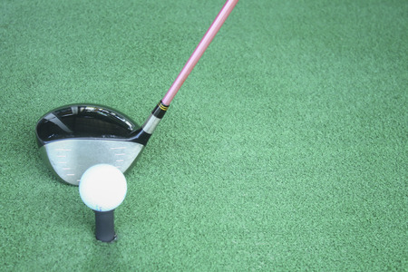 golf ball on tee with driver club, in front of driver, driving range