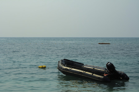 Rescue Boat in the seaof rescue unit to take care of tourist in the sea,Empty black rubber boat and blue sky Stock Photo
