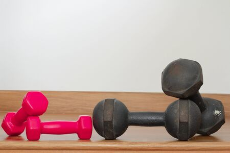 Old iron dumbbells and Red modern dumbbells on a wooden floor