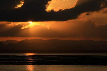 shining through: Tramonto sulla spiaggia e splende attraverso la nube