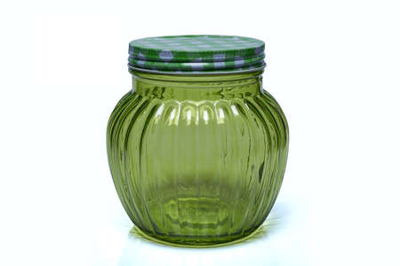 The glass jar, green color with metal lid isolated on white background