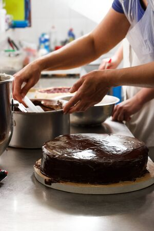 Woman smears chocolate cake with glaze icing, final stage of cooking. The process of making the chocolate cake, from begin to the end. Made by hands for confectionery. Foto de archivo