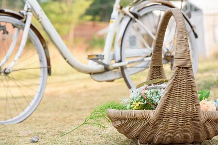 Bouquet in wicker baskets placed in the garden with old bicycle background