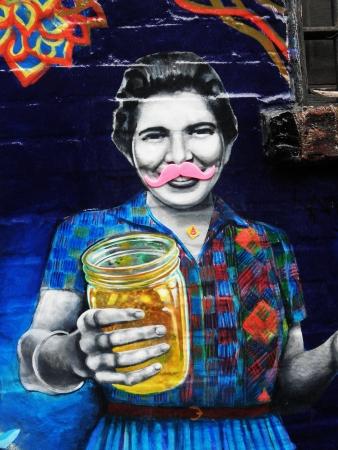 asheville: street art painting of woman holding jar in Asheville, North Carolina