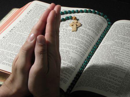 Biddende handen over grote Open Bijbel met gebed kralen
