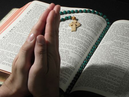 Praying Hands over Large Open Bible with Prayer Beads photo