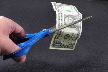 Cutting money with Scissors Stock Photo