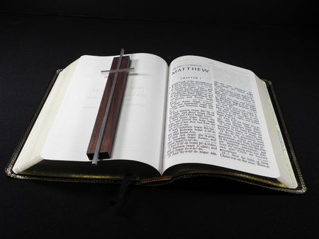 pious: Open Bible with Silver and Wood Cross Overlaid