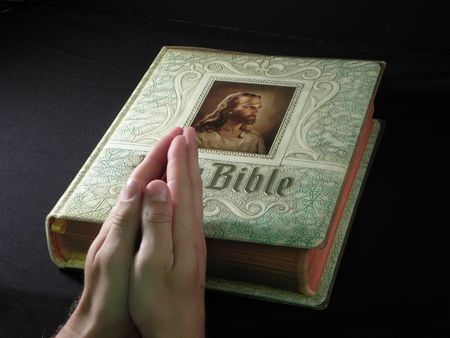devout: Praying Hands Over Closed Bible with Jesus Christ