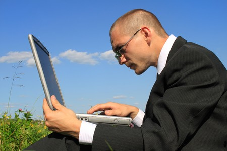 The young businessman in the field with the personal computer photo
