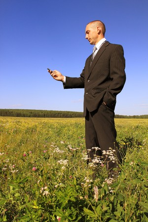 The young businessman in the field with a mobile phone photo