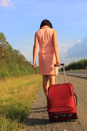 mujer con maleta: Mujer tirando su maleta detrás de ella, al lado de una carretera