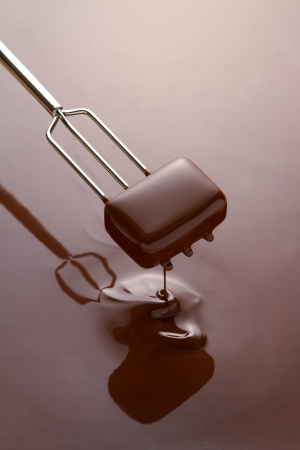 Dipping a chocolate in melted couverture chocolate