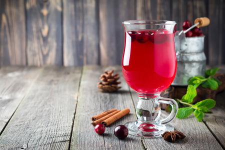 cranberry juice: Fresh cranberry juice with cinnamon and anise in glass jars on the old wooden background. Selective focus. Stock Photo