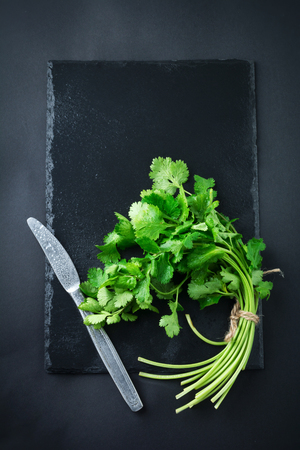 pectin: Fresh green coriander, coriander leaves on a black background. Selective focus.