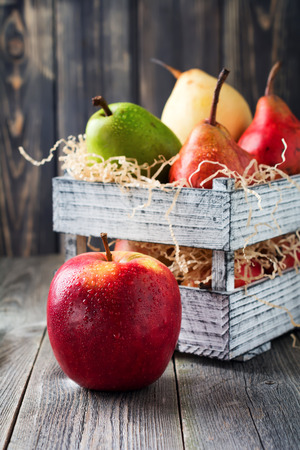 Red, green, yellow, sweet pear and one apple in the old wooden box on a dark background. Selective fokus.Rustik style Stock Photo
