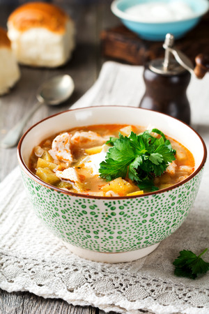 Traditional Russian soup-Rassolnik  wit hpickled cucumber, barley, chicken, tomatoes and parsley in ceramic bowl. Selective focus.  Stock Photo