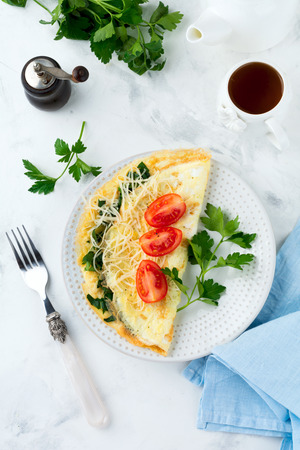 generosa: Omelet with spinach, parsley and cheese for breakfast on a light background. Selective focus.
