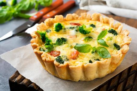 Eigengemaakte quiche scherp met rode vissenzalm, broccoli, basilicum, kruiden en kaas op een grijze steenachtergrond. Selectieve aandacht. Stockfoto