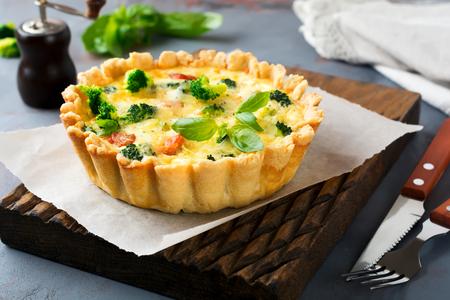 自家製キッシュ赤魚サーモン、ブロッコリー、バジル、調味料と灰色の石背景にチーズのタルト選択と集中。 写真素材