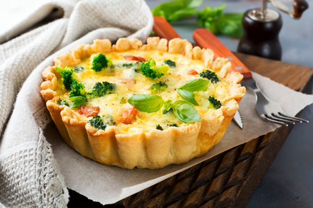 microelements: Homemade quiche tart with red fish salmon, broccoli, basil, seasonings and cheese on a gray stone background. Selective focus.
