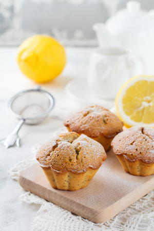 Lemon muffins with poppy seeds on a wooden stand on a light background. Selective focus. Stock Photo