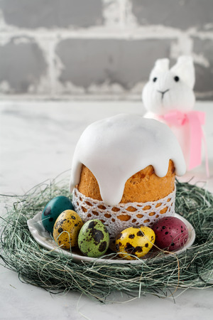Traditional Orthodox Easter bread Kulich with colorful quail eggs on a light background. Selective focus.