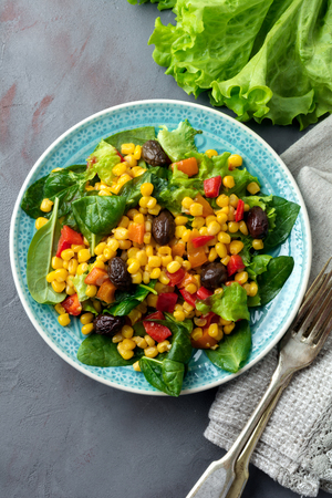 unspecified:  Warm salad with corn, pepper, olives and lettuce on a blue ceramic plate on a dark background. Selective focus.Top view.