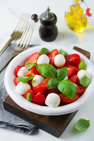 old desk: Traditional Italian caprese salad with tomatoes, mozzarella cheese and basil on a light marble background in a white old ceramic plate. Selective focus.Top view. Copy space. Stock Photo