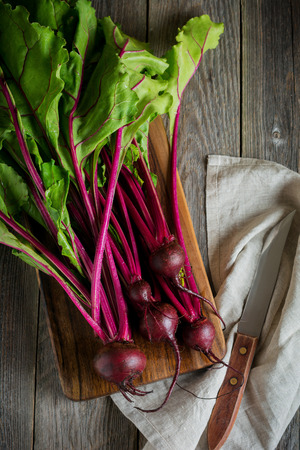 limited: Fresh young organic beet on a wooden background. Selective focus.Top view. Stock Photo