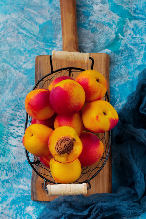 Fresh juicy fruit nectarines in  metal grid on blue concrete background. Selective focus. Top view. Rustic style. Stock Photo