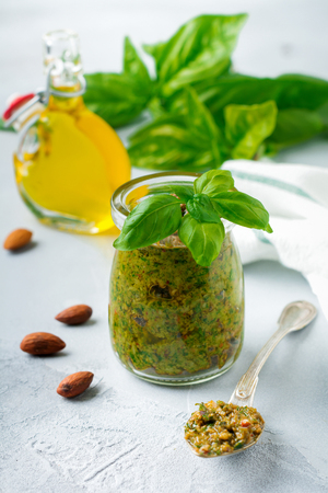 Homemade delicious green pesto in a glass jar. On a gray concrete background. Traditional Italian sauce. Selective focus.