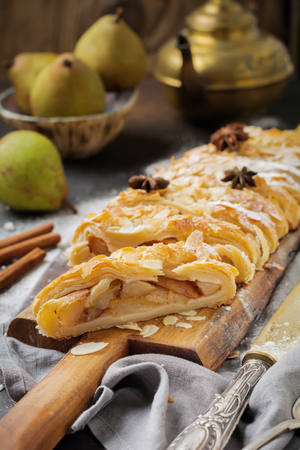 Homemade pear strudel, decorated with almonds, anise and powdered sugar on a rustic background. Selective focus. Top view.