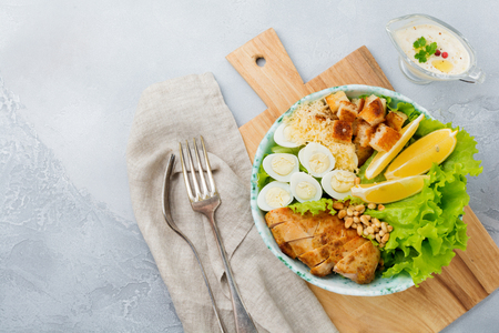 Traditional Caesar Salad with quail eggs and pine nuts in a light ceramic bowl On a gray stone or concrete background. Lunch bowl. Selective focus. Top view.