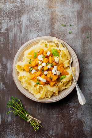 Pasta Mafaldine Napoletane with baked pumpkin, feta cheese and seasoning herbs in ceramic plate on gray concrete old background. Selective focus. Rustic style. Top view. Stockfoto